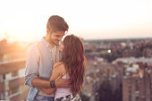 Couple in love standing and hugging on a building rooftop at sunset with cityscape in the background. Focus on the girl
