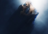 Couple in love. Sensual brunette and handsome man kissing. Image with a blurry effect