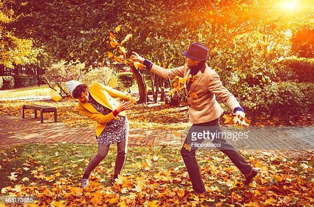 Couple de passion en jouant avec les feuilles dans le parc