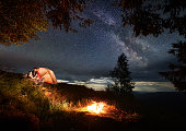 Couple backpackers in love sitting on a hill near the glowing orange tent, enjoying a burning fire under the night sky with bright stars and milky way. Powerful mountains and hills in the distance