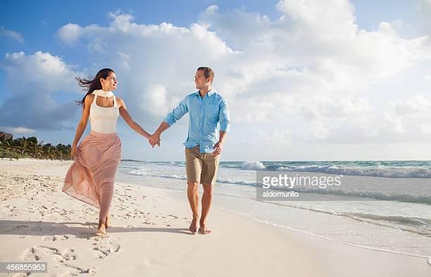 En amor pareja sosteniendo las manos y caminar en la playa