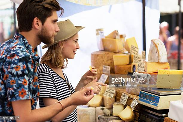 Couple in market at cheese stall