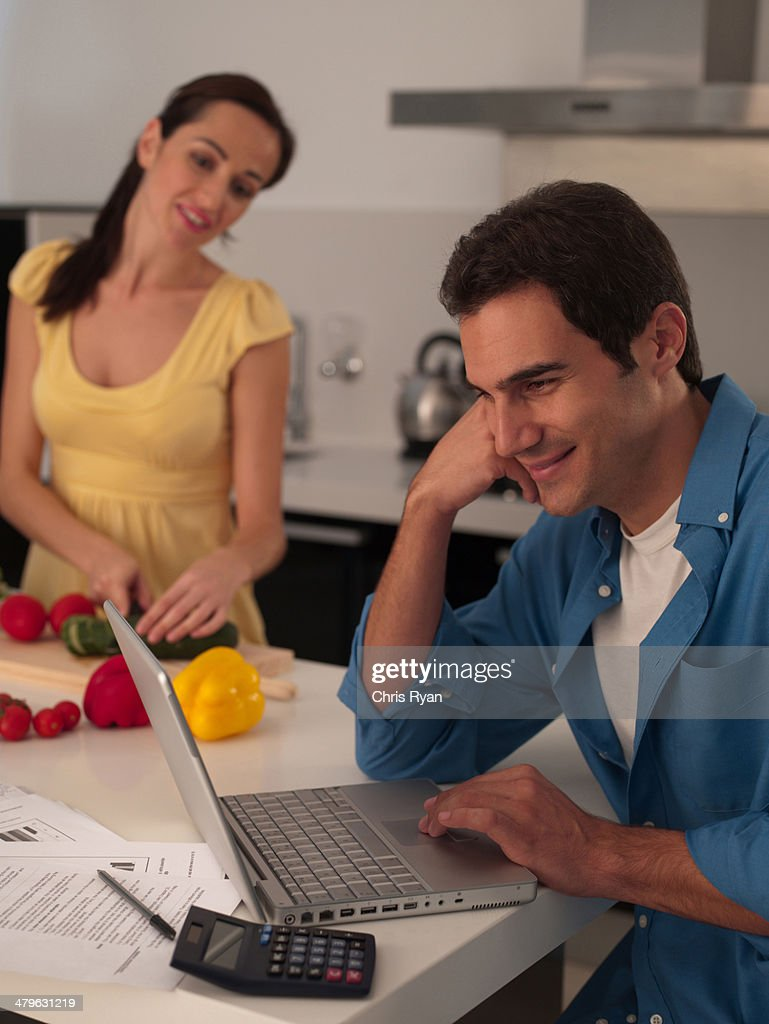 Couple in modern kitchen man working on laptop with woman preparing a meal : Stock Photo