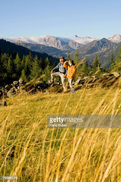 'Couple in mountains, standing in meadow'