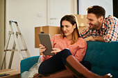Young heterosexual couple surrounded with unpacked cardboard boxes resting on the sofa in their new apartment and looking at digital tablet.