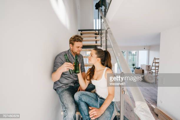 Couple in new home sitting on stairs, toasting with bottles of beer
