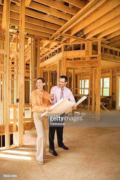 Couple in new house with blueprints