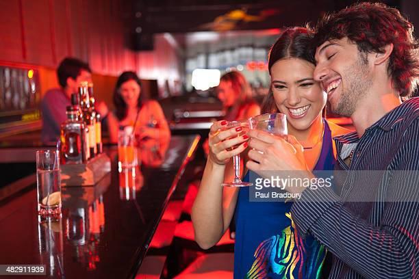 Coppia in discoteca e sorridente brindando