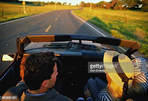 Couple in open top car driving in country,woman in straw hat