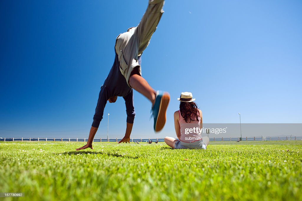 Couple in park with male doing summersaults