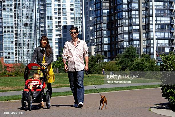 Couple in park, woman pushing pushchair, man holding dog's lead