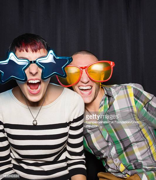 Couple in photo booth wearing oversized sunglasses