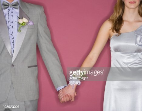 Couple in prom attire holding hands