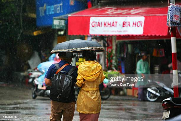 couple in rain walking on hanoi old quarter to visit