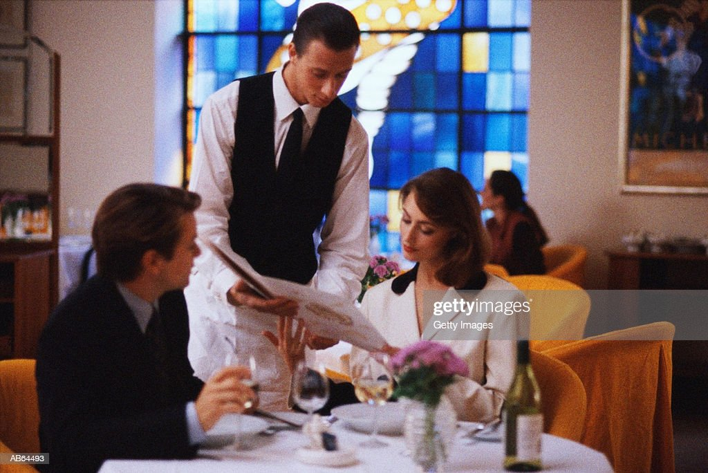 Couple in restaurant ordering meal with waiter : Stock Photo