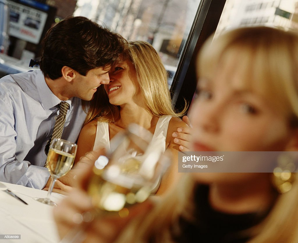 Couple in restaurant, woman drinking wine  in foreground : Stock Photo