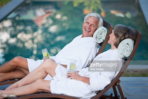Couple in robes relaxing in lounge chairs at poolside