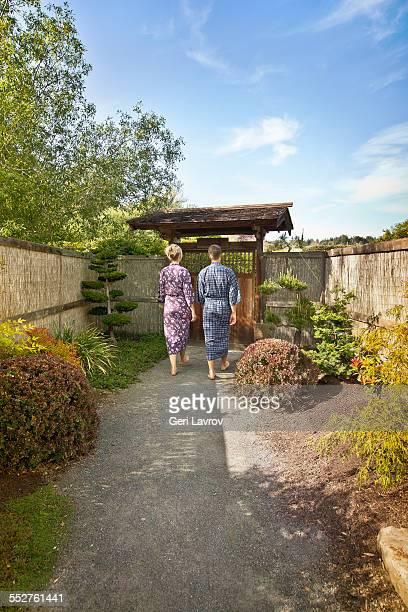 Couple in robes walking in a zen garden