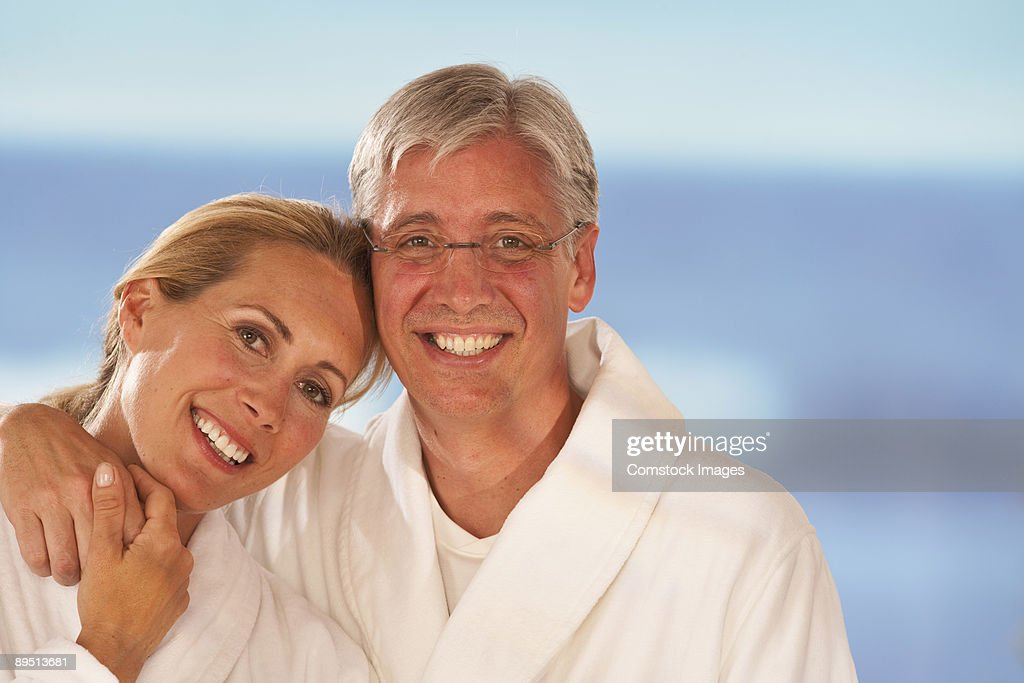 couple in robs relaxing by the ocean : Stock Photo