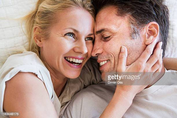 Couple in romantic embrace, woman laughing