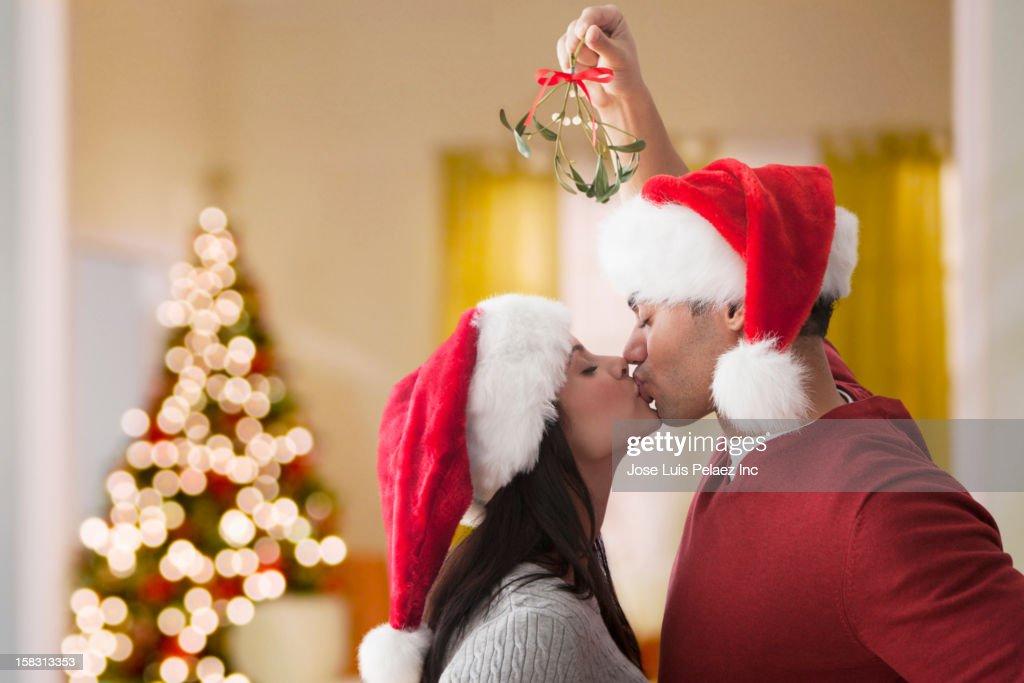 Couple in Santa hats kissing underneath mistletoe