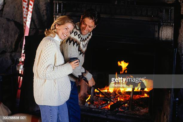 Couple in ski lodge standing  by fireplace, man stoking fire