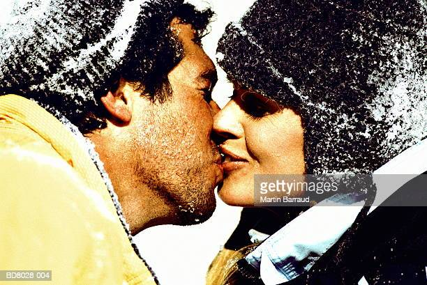 Couple in snow kissing, close-up, profile