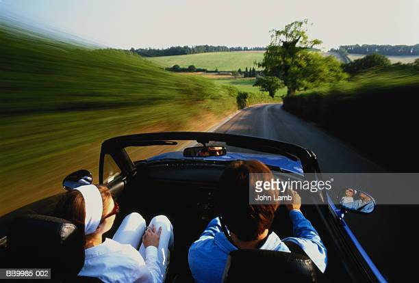 Couple in sports car on country lane, rear view (blurred motion)