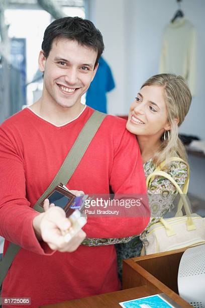 Couple in store at cashier where the man is paying with a credit card smiling