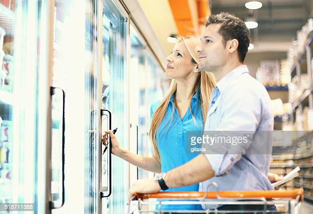 Couple in supermarket buying frozen food.