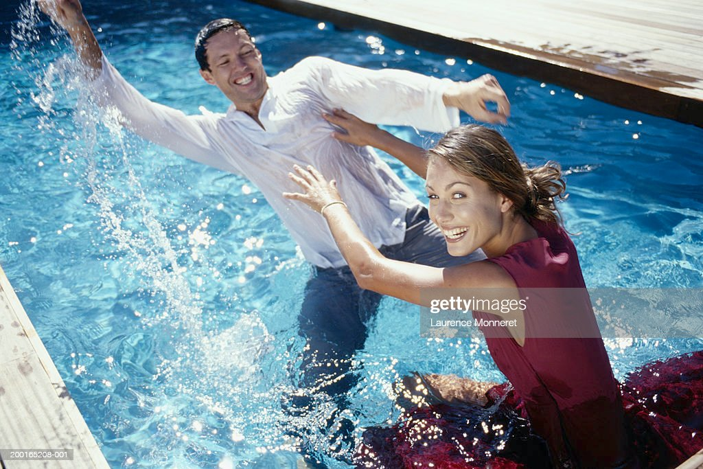 Swimming Pool Clothing : Couple in swimming pool with clothes on having water fight