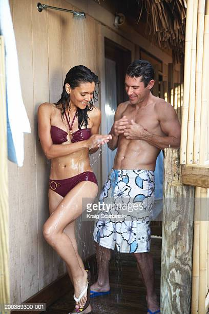 Couple in swimsuits rinsing off in outdoor shower