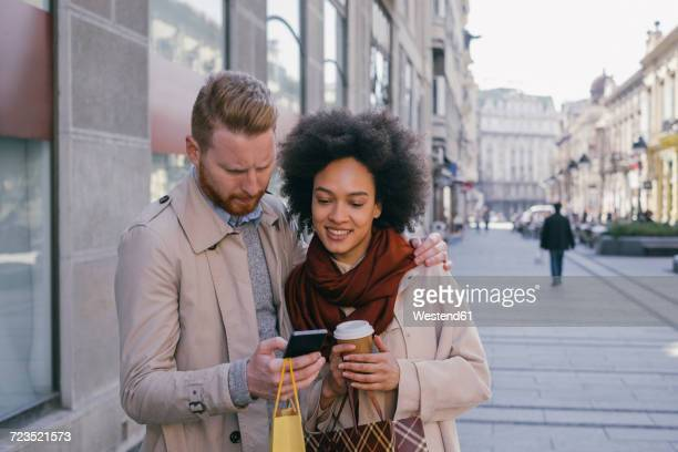 Couple in the city with cell phone and shopping bags