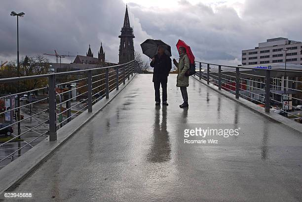 Couple in the rain on bridge with umbrellas, evening.