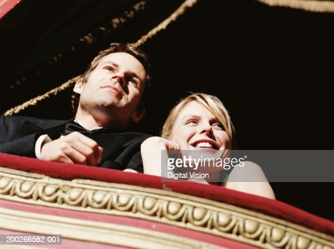 Couple in theatre box, smiling, low angle view : Stock Photo