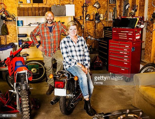 Couple in their motorcycle garage workshop