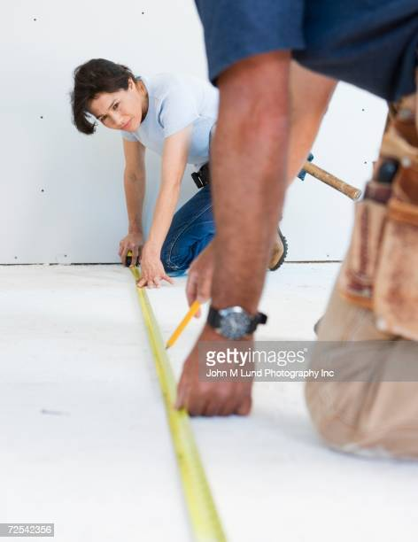 Couple in tool belts measuring floor