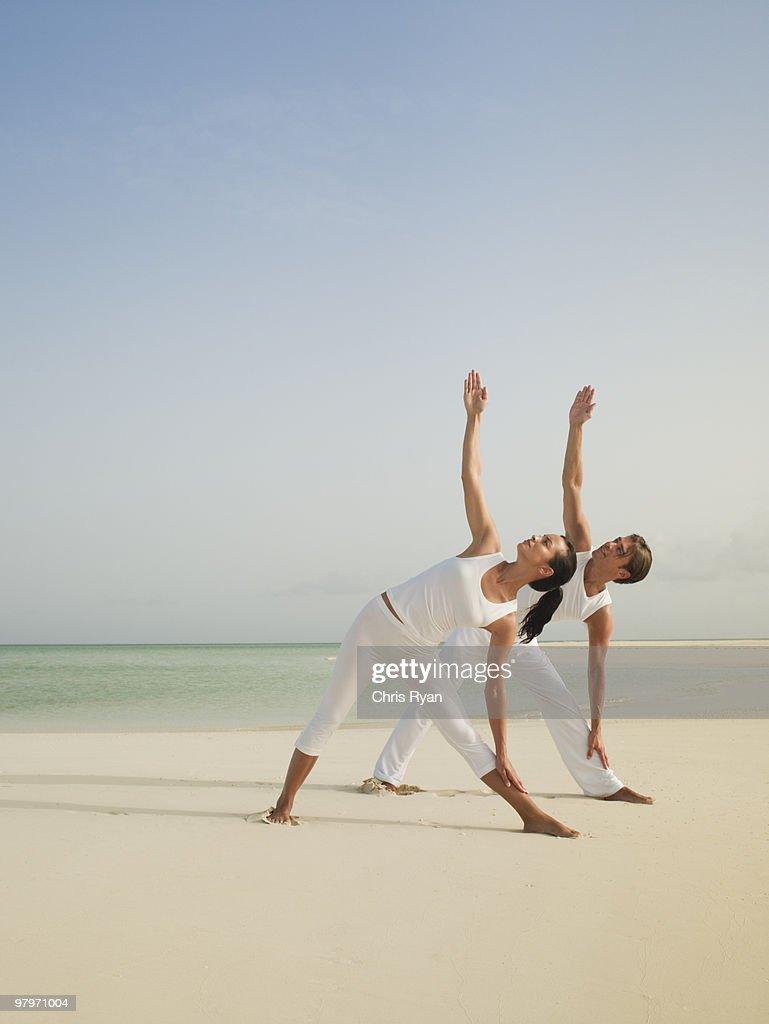 Couple in triangle yoga pose on beach : Stock Photo