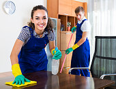 Young couple in uniform smiling and cleaning indoors