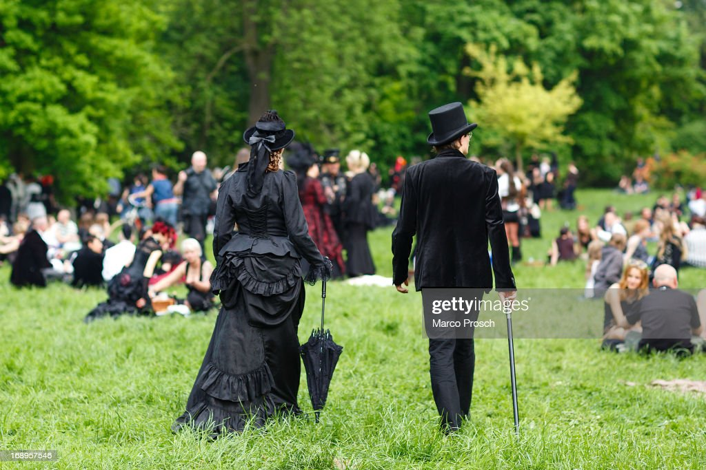 A couple in Victorian clothing walks on the lawn during the traditional park picnic on the first day of the annual Wave-Gotik Treffen, or Wave and Goth Festival, on May 17, 2013 in Leipzig, Germany. The four-day festival, in which elaborate fashion is a must, brings together over 20,000 Wave, Goth and steam punk enthusiasts from all over the world for concerts, readings, films, a Middle Ages market and workshops.