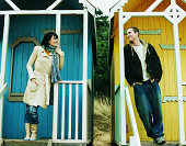 Couple in Warm Clothing Stand Outside Beach Huts Looking at Each Other