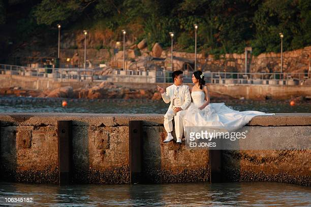 A couple in wedding dress pose for a photographer as they sit on a wall at a beach in the Stanley district of Hong Kong on October 29 2010 During...