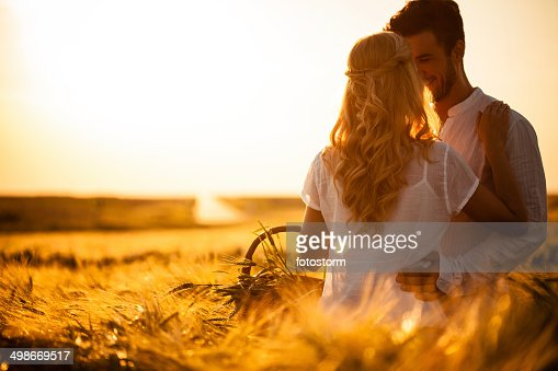 Couple in wheat field at sunset