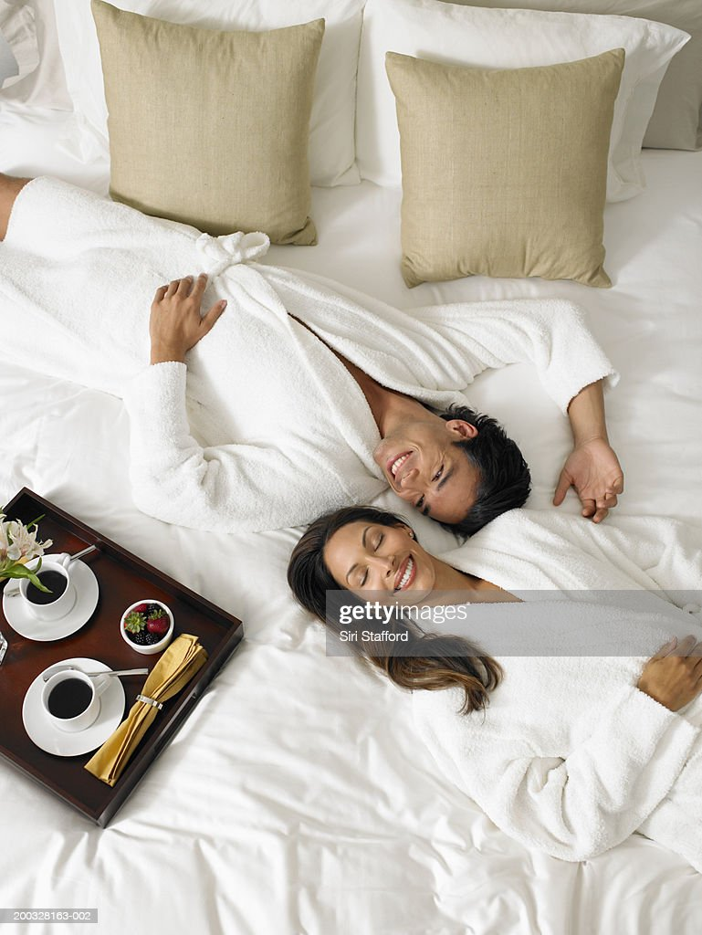 Couple in white bathrobes lying on bed, breakfast tray on side : Stock Photo
