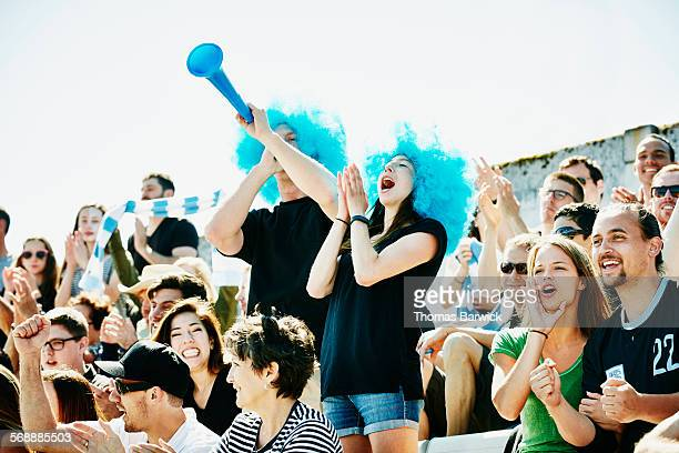 Couple in wigs leading cheer during soccer match
