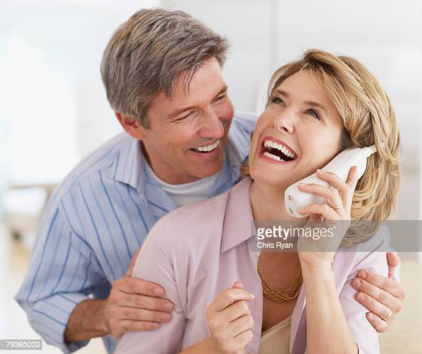 Couple indoors with a telephone laughing