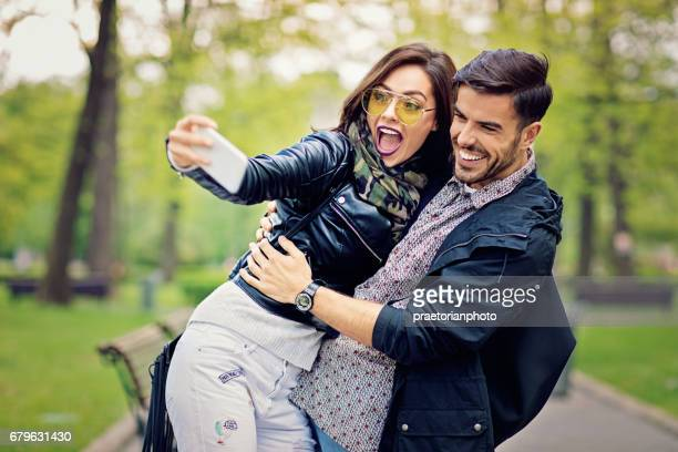 Couple is hugging and taking selfie in the park