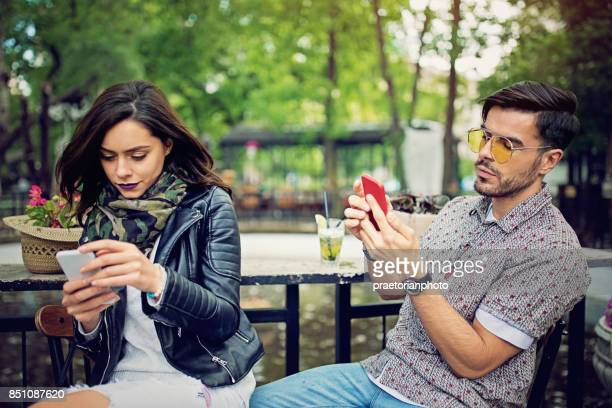 Couple is looking in their mobile phones and sulking each other in the cafe