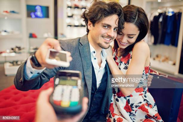Couple is making contactless payment using mobile phone in the Mall
