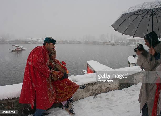 A couple is photographed on the bank of Dal lake amid heavy snowfall on December 31 in Srinagar the summer capital of Indian administered Kashmir...